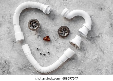 Disassembled face-like sink drain pipe heart shaped on grey stone background top view