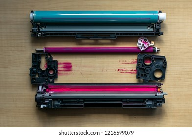 Disassembled into parts of the color cartridge from the laser printer is on a wooden table