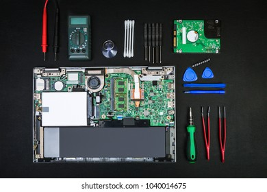 Disassembled laptop with computer parts and special tools for repair on a black desk. The concept of computer repair in flat lay style