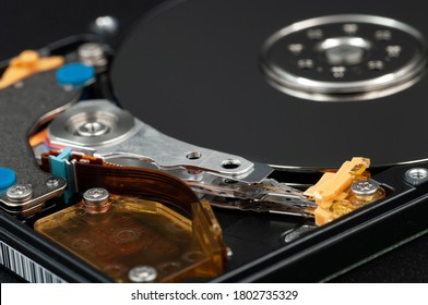 Disassembled laptop hard disk drive, hdd. Close-up. Opened hard drive, magnetic heads and disk plates