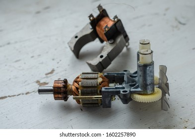 Disassembled motor for used kitchen mixer. Stator and rotor on a light table. Service and repair of household appliances. Selective focus. Without people. Close-up.