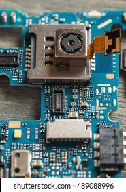 Disassembled parts of cell phone close-up shot, selective focus, repair and service concept, vertical