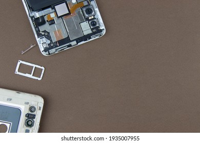 disassembled parts of the smartphone on a brown background,the concept of computer hardware, mobile phone, electronic, repairing, upgrade and technology.