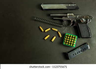 Disassembled pistol on black background. Separated pistol parts. Gun and cartridges on the table. Right to hold a gun