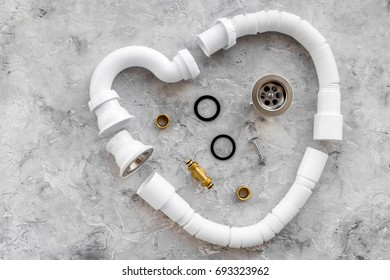 Disassembled sink drain pipe heart shaped on grey stone background top view