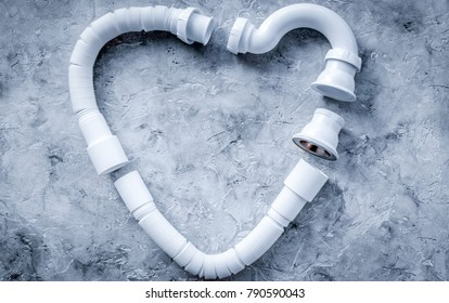 Disassembled sink drain pipe heart shaped on grey stone backgrou