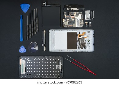 The disassembled smartphone with the removed screen and special purpose tools on the black desktop. Cell phone details in flatlay style.