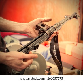 disassembled submachine gun MP-38 in the hands of a master. Gun locksmith workshop. instagram image retro style