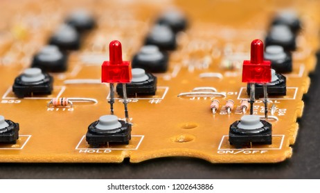 Disassembled telephone. Red LED diodes and gray buttons. Yellow circuit board with plastic pushbuttons. Electronic components on dismantled VoIP phone keypad. Telecommunications. Small depth of field.