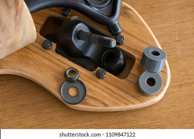 disassembled truck and bushings of longboard on a wooden background