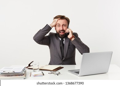 It's a disaster, everything goes wrong, OMG! Respectable office worker sitting at table grasping his head, nervous, is in a difficult situation, holding a phone near his ear, screams from panic