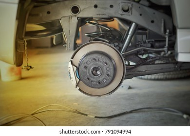 Disc brake on car in process of new tire replacement. The rim is removed showing the rotor and caliper.close up.