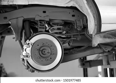 Disc brake of the vehicle for repair, in process of new tire replacement. Car brake repairing in garage.Suspension of car for maintenance brakes and shock absorber systems.Close up.