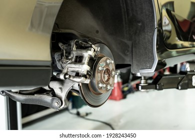 Disc car close up - mechanic unscrewing automobile parts while working under a lifted auto - Car service concept