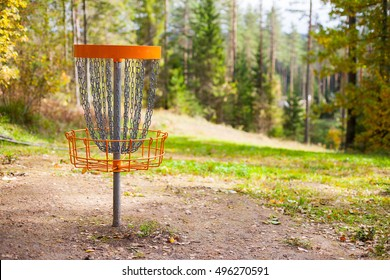 Disc golf (frolf) basket on a forest course in autumn with a shallow depth of field