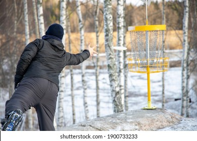 Disc golf player putting to basket
