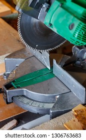 The disc of the green electrical circular mitre saw standing on the workbench in the carpenter workroom. Soft focus.