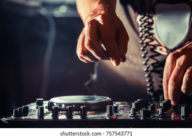Disc jockey at the turntable. DJ plays on the best, famous CD players at nightclub during party. EDM, party nightlife concept. Dj hands on the turntables.