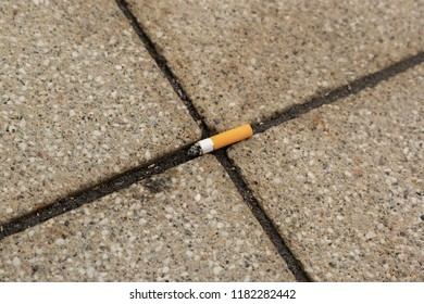 A discarded cigarette lies on the floor