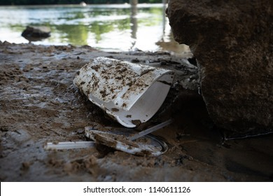 Discarded food containers litter the area under a bridge near a river with trash that includes plastic straws, plastic lids, a Styrofoam cup and other plastic food waste, contributing to pollution.