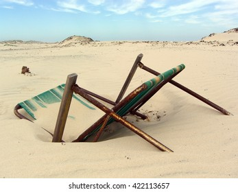 Discarded old lawn chair buried in the sand and rusting