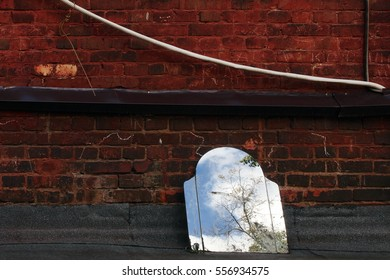 A discarded old mirror with a reflection of a tree and a fragment of the sky, on the background of a brick wall. Russia, Moscow, August 2016.