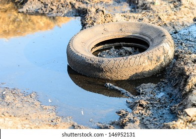A discarded old tyre in a puddle of contaminated water