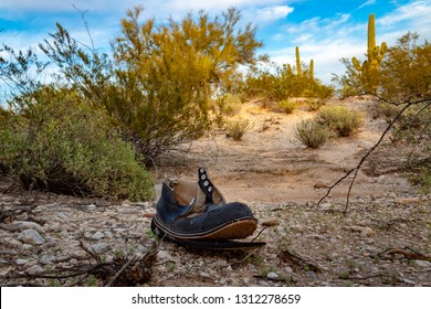A discarded old work boot or hiking shoe abandoned in the middle of the Sonoran Desert where the harsh elements have taken a toll on the footwear. Blue sky with white clouds. Tucson, Arizona. 2019.