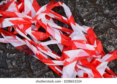 A discarded pile of red and white barrier tape lying on the ground