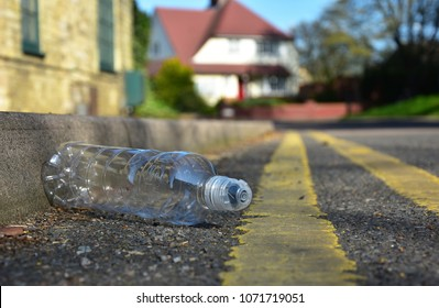 A discarded plastic bottle lies in the gutter at the side of an urban street with yellow lines