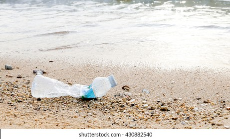 A discarded plastic bottle lies on a lifeless, black sandy seabed