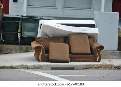 Discarded sofa left out on the sidewalk for garbage pickup in impoverished urban neighborhood