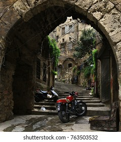 A discarded sofa with two motorcycles parked in an old alleyway in Tripoli, Lebanon.