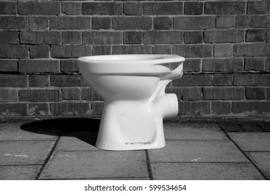discarded toilet on street black and white