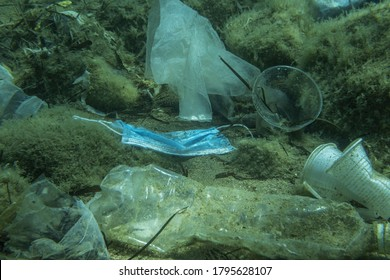 Discarded used medical face mask along with other plastic debris lies on the seabed.