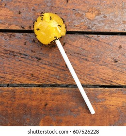 Discarded yellow round lollipop covered in ants on a wooden table