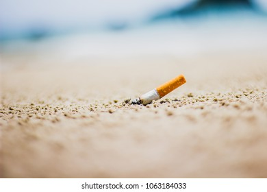 Discarding cigarette butts on the beach, sand is not good , soft focus , blurred.