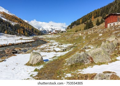 Dischma valley with the river Dischmabach, a hiking trail and large rocks in Davos in Grisons, Switzerland. Alpine autumn landscape with snow.