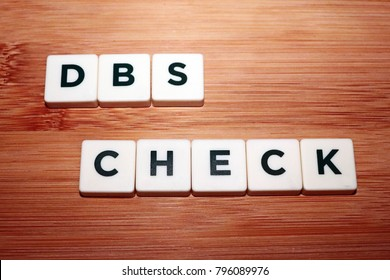 """""""Disclosure and Barring Service (DBS) Check"""" Board Game Tiles on Wooden Background"""