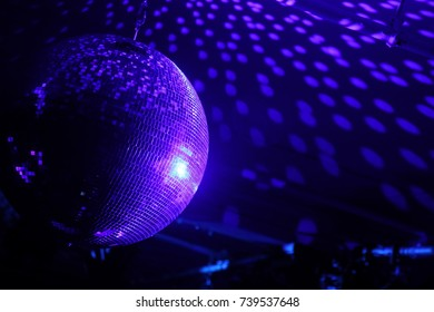 Disco ball with bright rays, night party background photo.