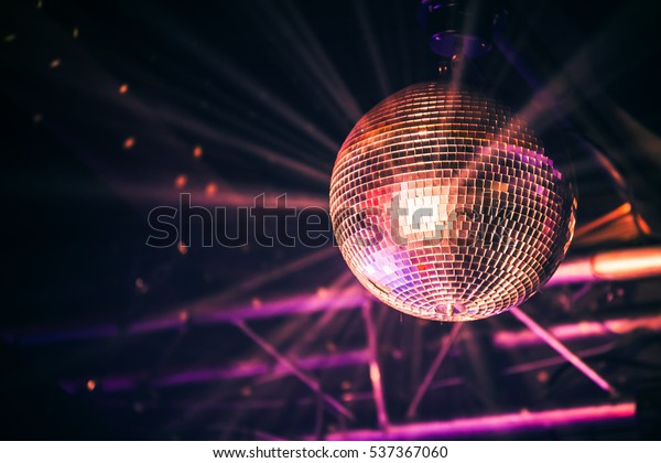 Disco ball with bright rays, night party background photo