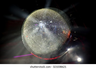 Disco ball hanging in the dark and floodlights
