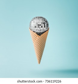 Disco ball ice cream on bright blue background. Minimal party concept.