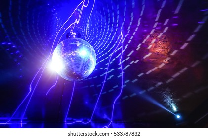 Disco ball laser show in modern disco party night club with bright spotlight - Concept of nightlife with music and entertainment - Image with powered colored halos and vivid glowing lights