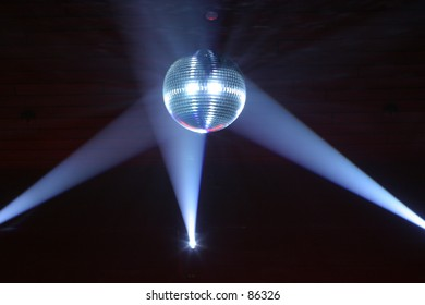Disco ball at a nightclub lit by spotlights.