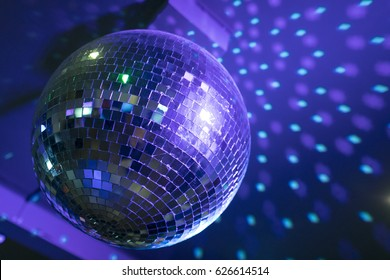 Disco ball reflecting purple and green lights from the ceiling