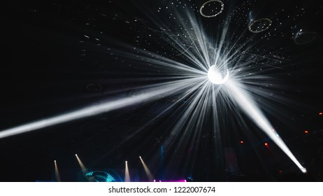 disco ball suspended to the ceiling in the club during the concert, shining with blue colour. mirrors reflect a bright light at discotheque. shoot from a distance