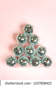 disco balls for decoration party on pastel pink gradient background. Light silver disco balls making a shape of fir tree. Christmas New year concept. top view, flat lay. Frame with room for copy.
