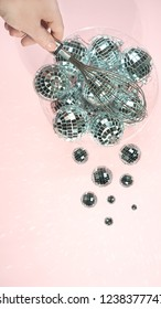 disco balls for decoration party shattering into small balls in a bowl with whisk in hand on pastel pink gradient background. Christmas New year holiday kitchen concept. top view, flat lay close up