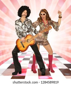Disco couple having fun playing the guitar and singing on a colorful background